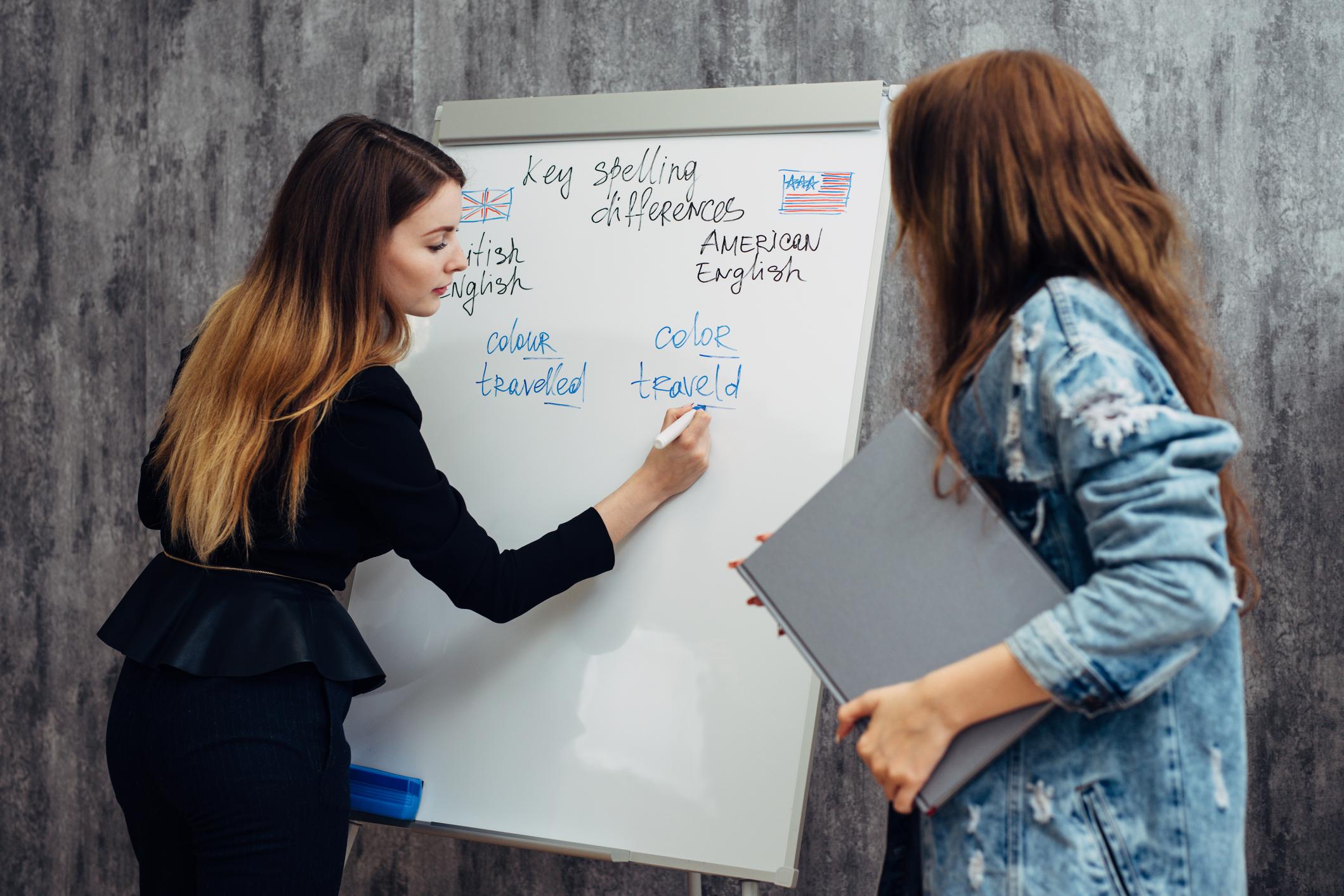 Nauczyciel uczy licealistę języka angielskiego na tabllicy w liceum