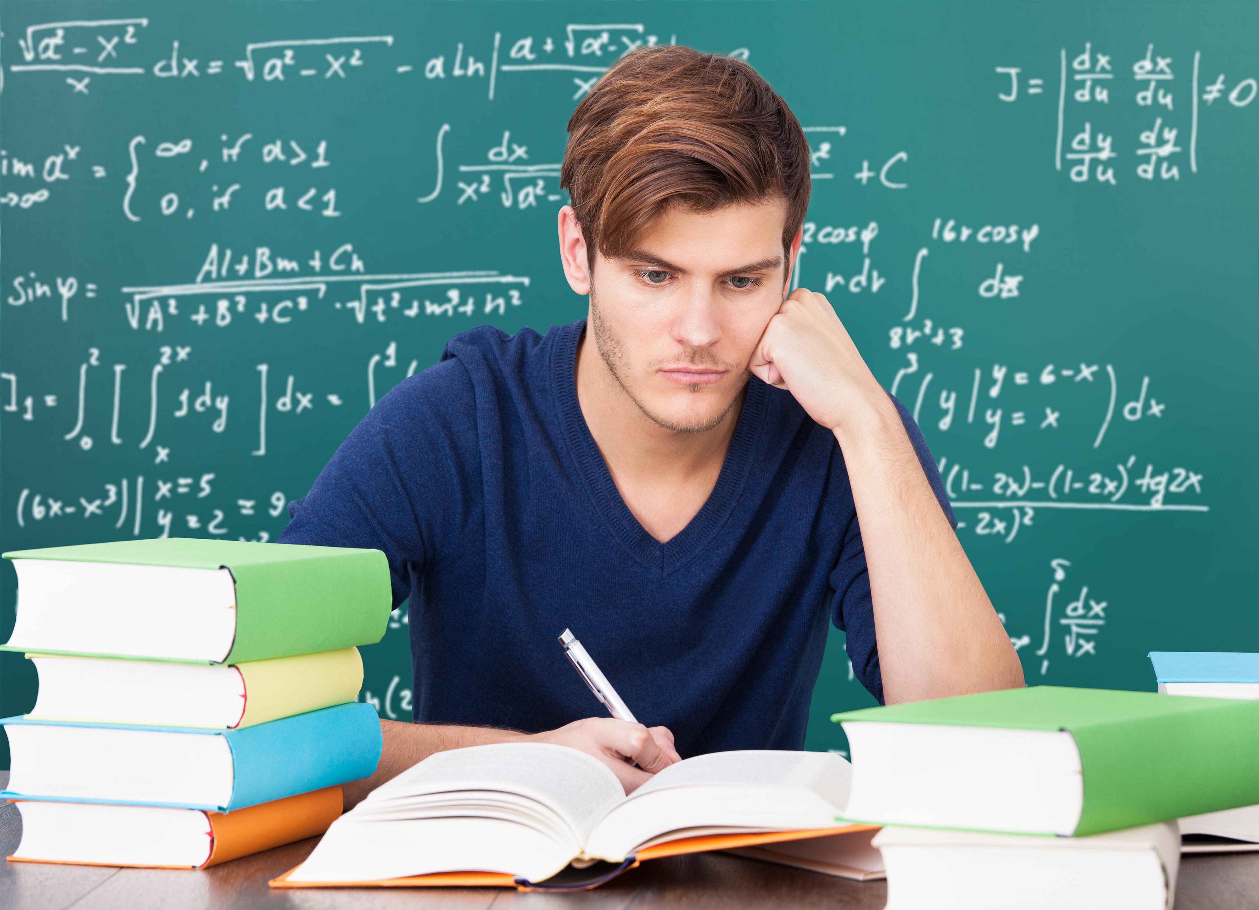 licealista siedzi przy biurku, uczy się i pisze pracę